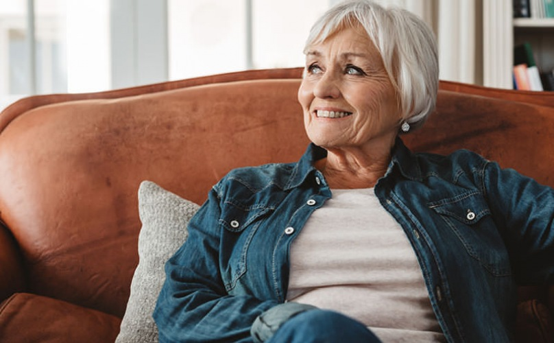 older woman smiles as she relaxes on her living room sofa