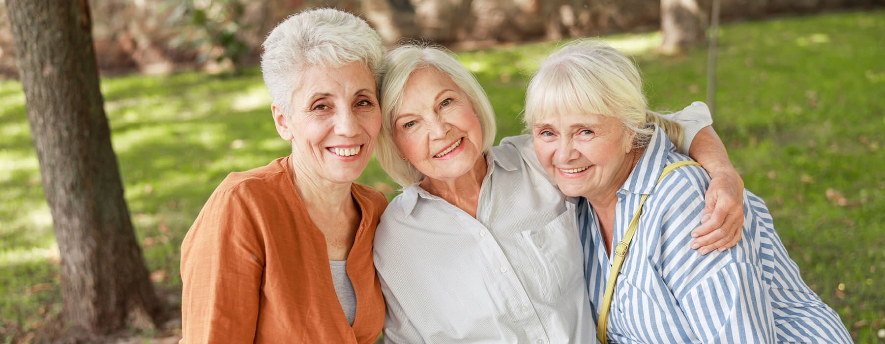 three women smile for the camera in a neighborhood park