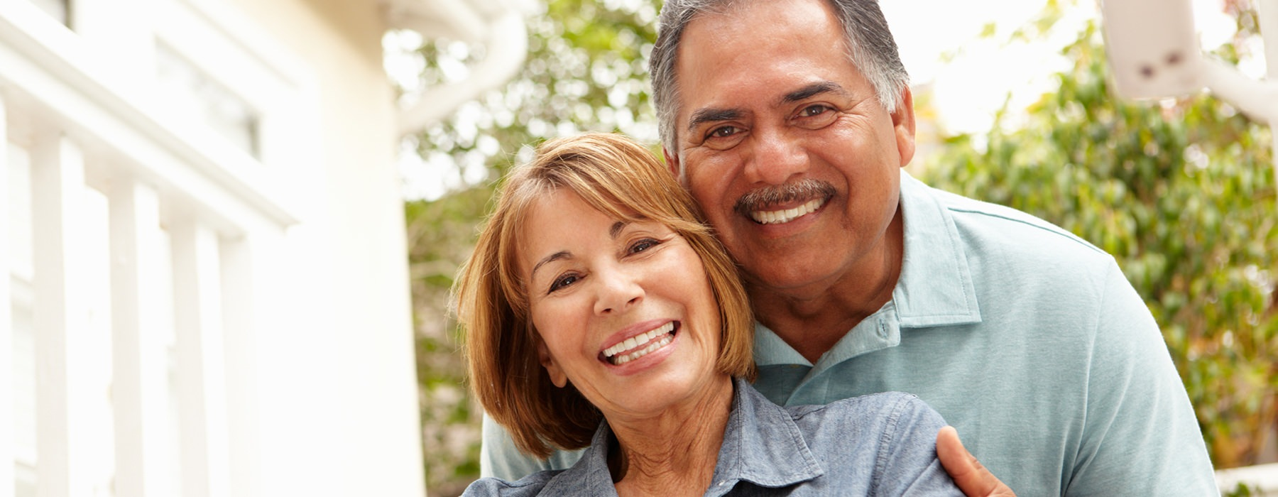 an older couple smiles for the camera outdoors
