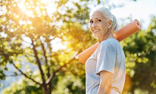 older woman carries a yoga mat at as she walks through nearby park